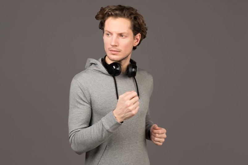 young man grey hoodie black headphones
